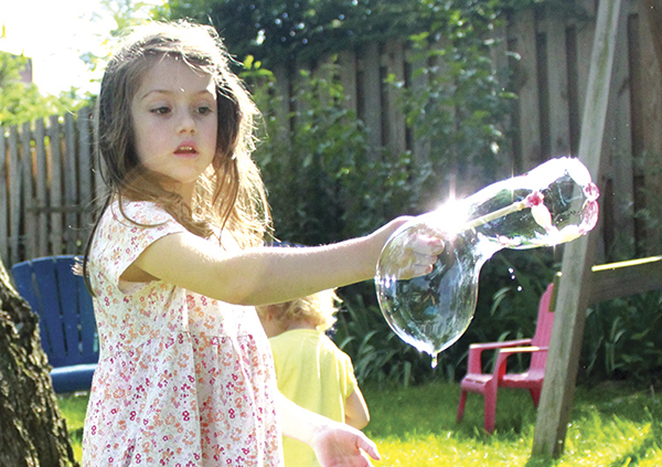 Girl is blowing bubbles with a beaded bubble wand, you make yourself.