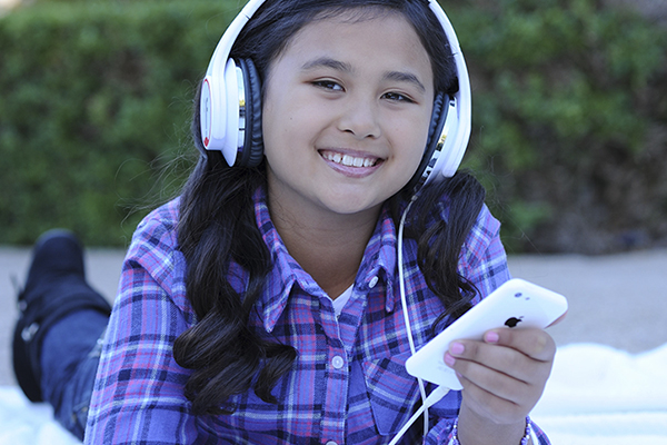 Girl listening to her music through headphones.