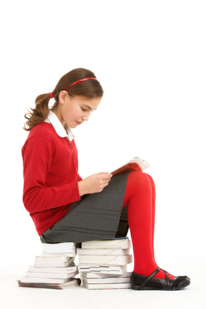 Young girl is sitting on a stack of books.