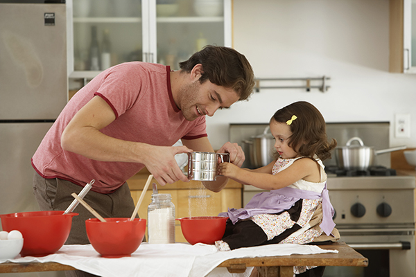 A father and daughter cook together.